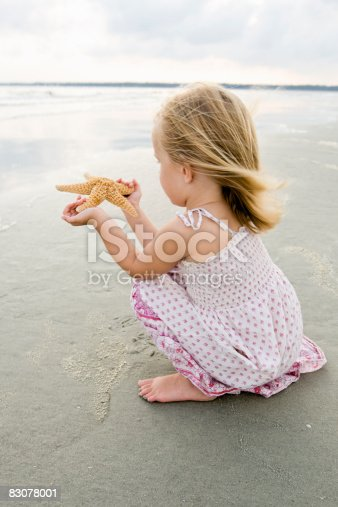 Young girl with starfish on the beach.