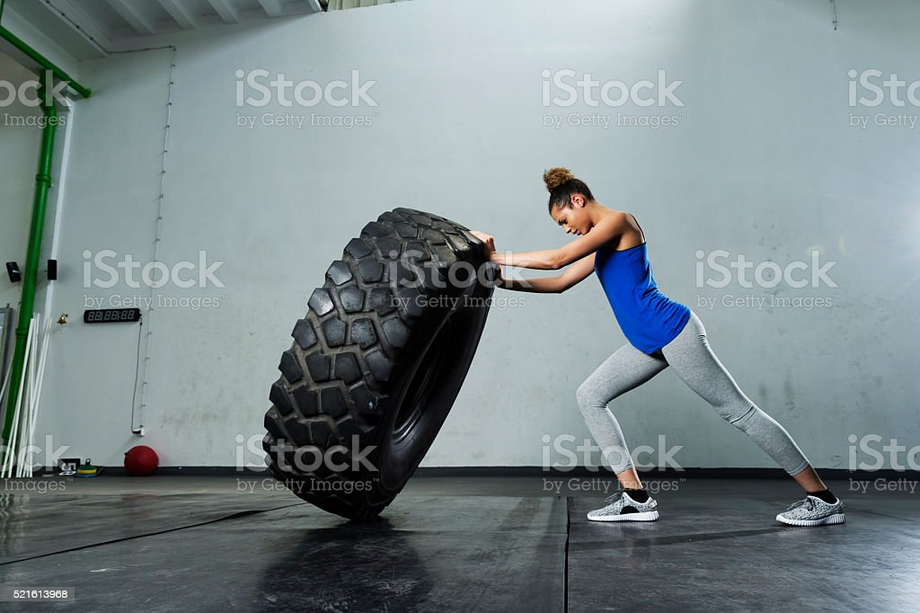 Young girl flipping tire at the gym stock photo