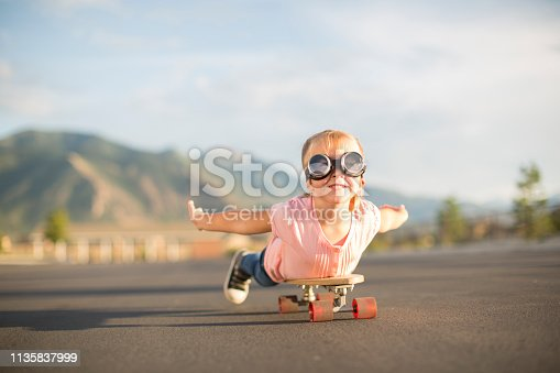 istock Young Girl Flying on Skateboard 1135837999