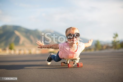 istock Young Girl Flying on Skateboard 1135838029