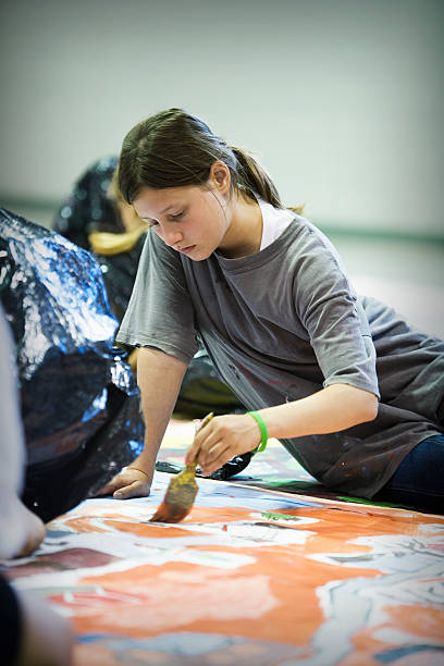 Young girl focusing on painting a mural on the floor stock photo