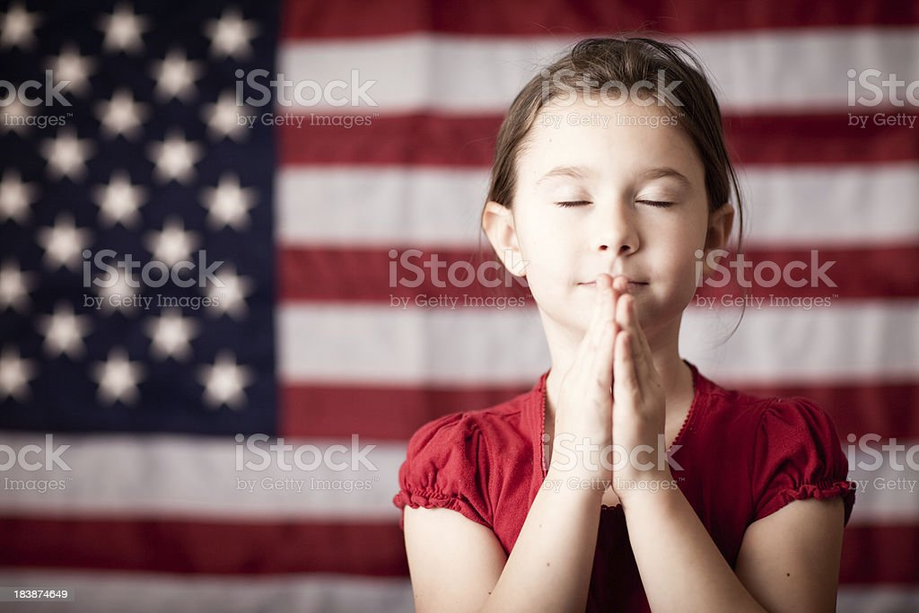 Young Girl Folding Hands and Praying by American Flag stock photo