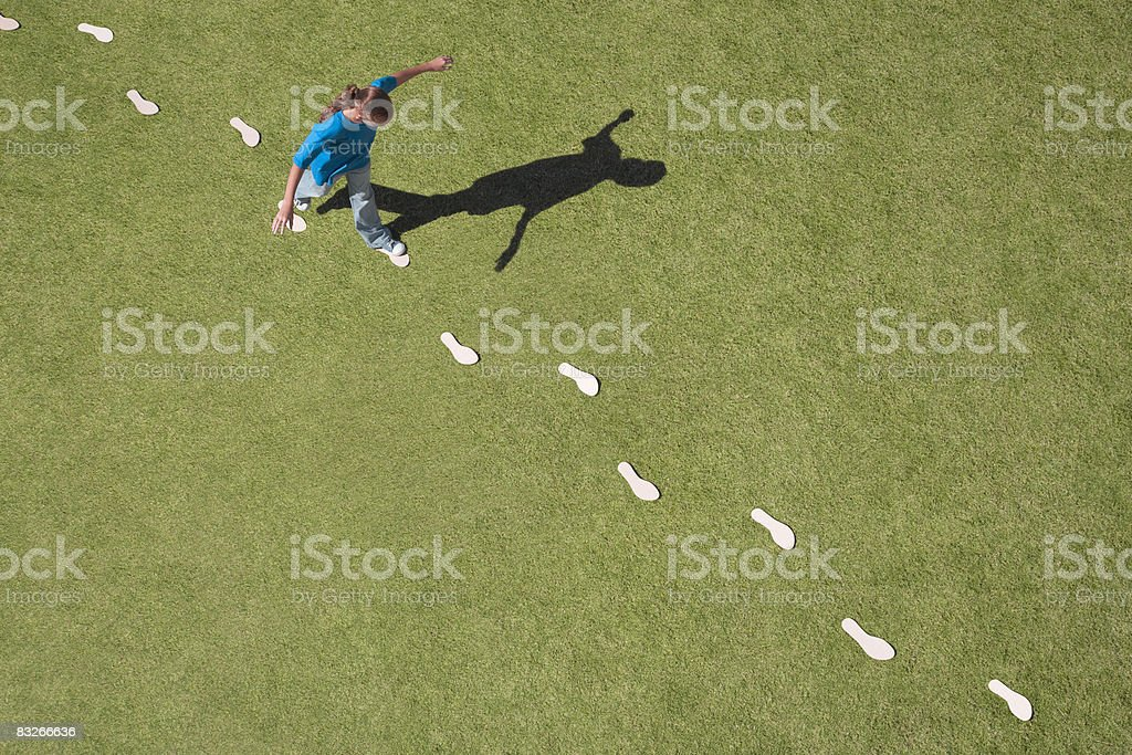 Young girl following footprints on grass stock photo