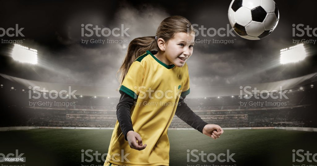 6f8445b37 Young girl football player heading a soccer ball in a floodlit stadium  royalty-free stock