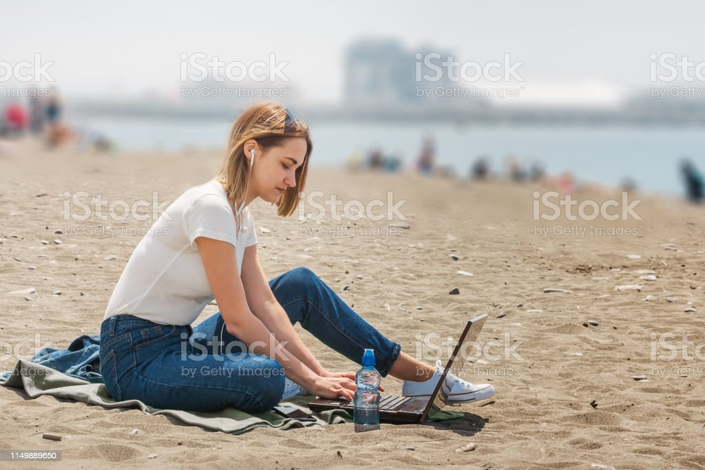 Young girl freelancer works with a laptop outdoors on the sea beach....
