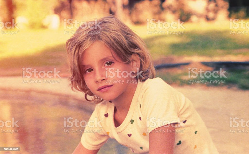 Young girl from looking at camera Vintage photo from the seventies featuring a girl lsitting at sunset outdoors and looking serious at camera. 1970-1979 Stock Photo