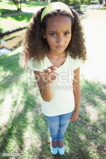 Young girl frowning and pointing at the camera in the park on a sunny day