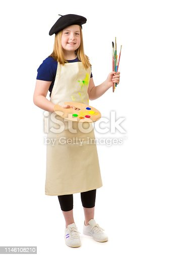 Young girl career aspiration of becoming an artist painter. She is holding a paint pallette and paint brushes.