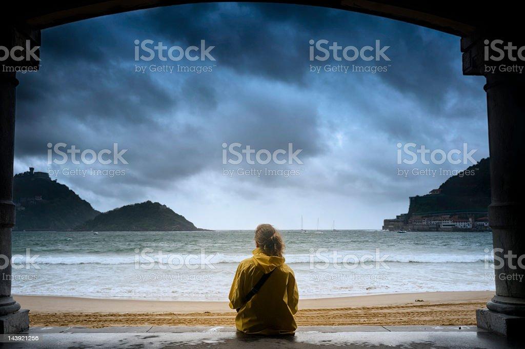 Young girl gazing at the ocean in San Sebastian stock photo
