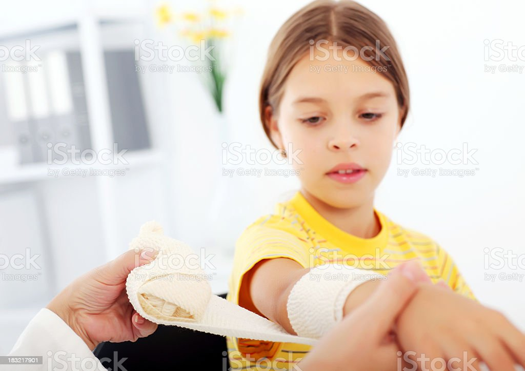 Young girl getting a bandage on her arm in hospital. royalty-free stock photo