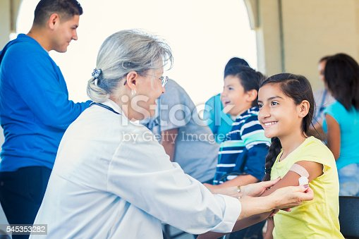 Pretty young girl getting a bandaid after receiving her flu shot. She is smiling up at her senior female doctor. She is a pretty hispanic girl wearing a yellow shirt. There are other volunteers and children behind them.