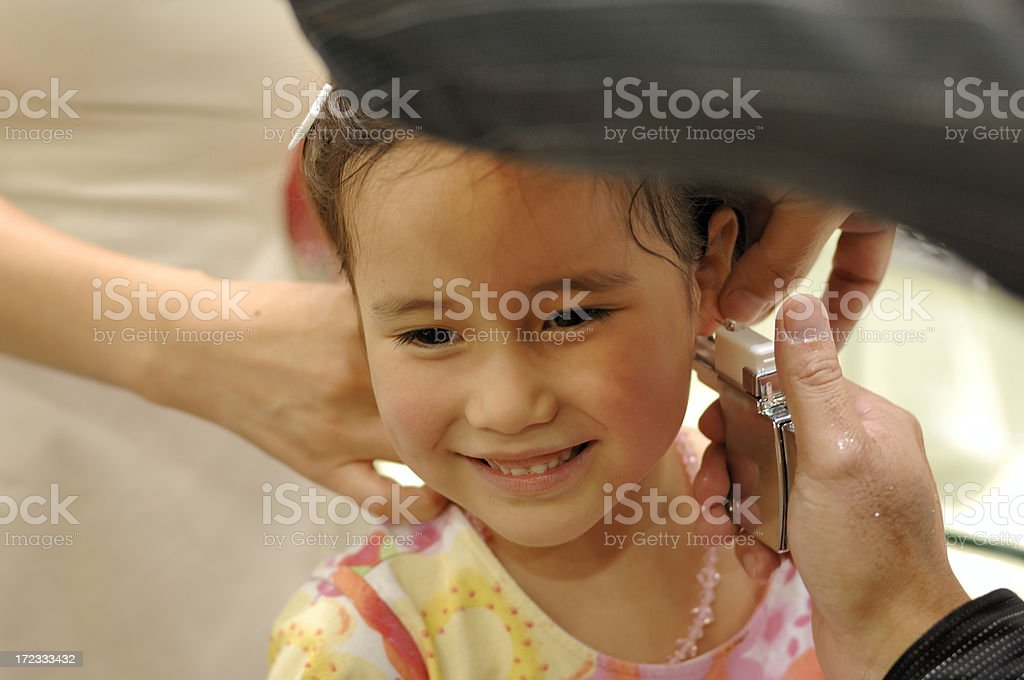 Young girl getting her ears pierced stock photo