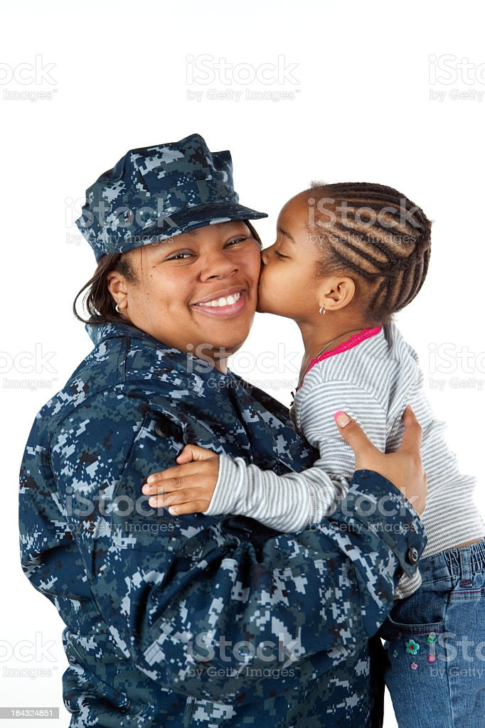 A young girl gives a kiss to her mom in a military uniform royalty-free stock photo