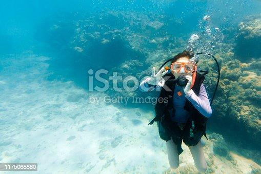 Young girl giving a ok sign while scuba diving in Maragogi, Alagoas, Northeastern Brazil