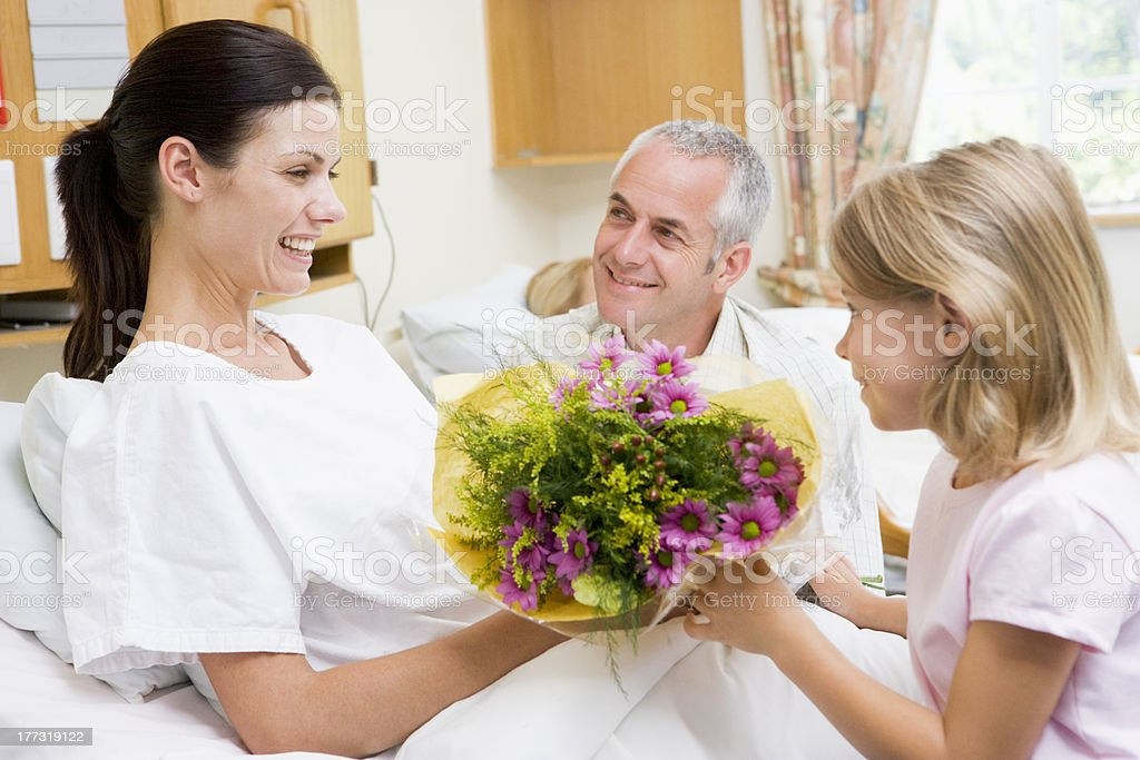 Young Girl Giving Flowers To Her Mother stock photo