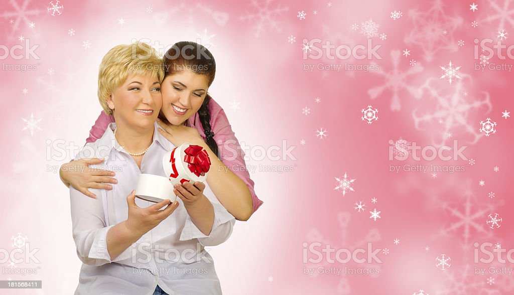 Young girl giving gift to her mother on winter background royalty-free stock photo