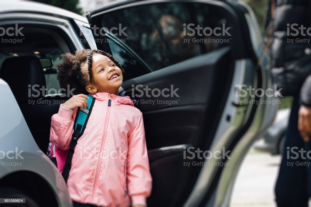 young girl going to school with parent stock photo