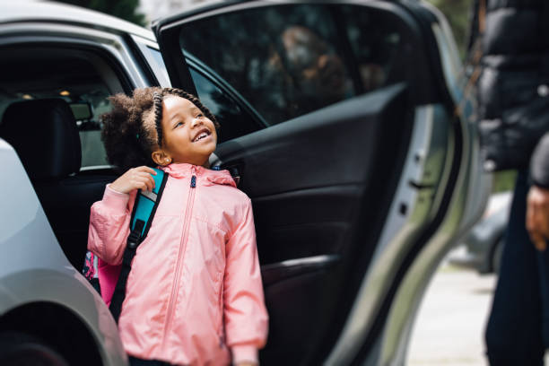 young girl going to school with parent Mother taking her daughter to school entering stock pictures, royalty-free photos & images