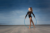 A young girl gymnast in a black bathing suit looks in profile in the hands of a gymnastic hoop.