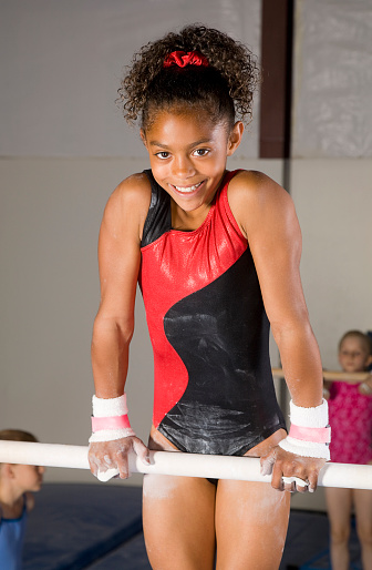 A young gymnast balancing on the parallel bars.