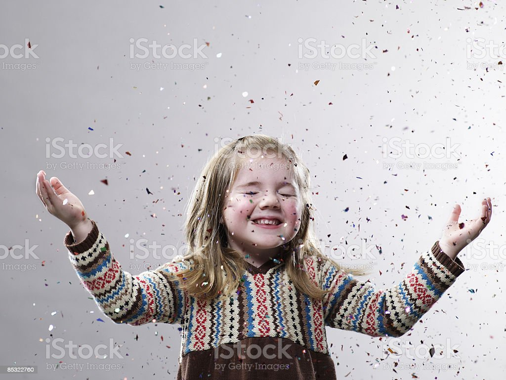 Young girl hands up with confetti flying royalty-free stock photo
