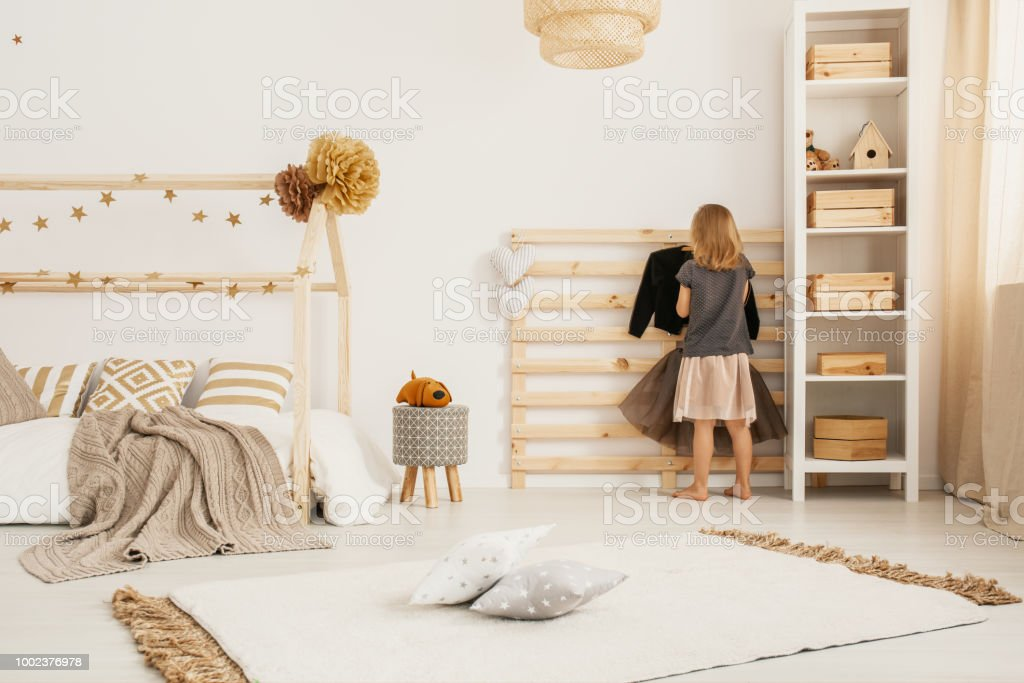 Young girl hanging clothes on wooden hanger in white Nordic style bedroom interior with home-shape bed, two pillows placed on carpet and white rack with wooden boxes stock photo