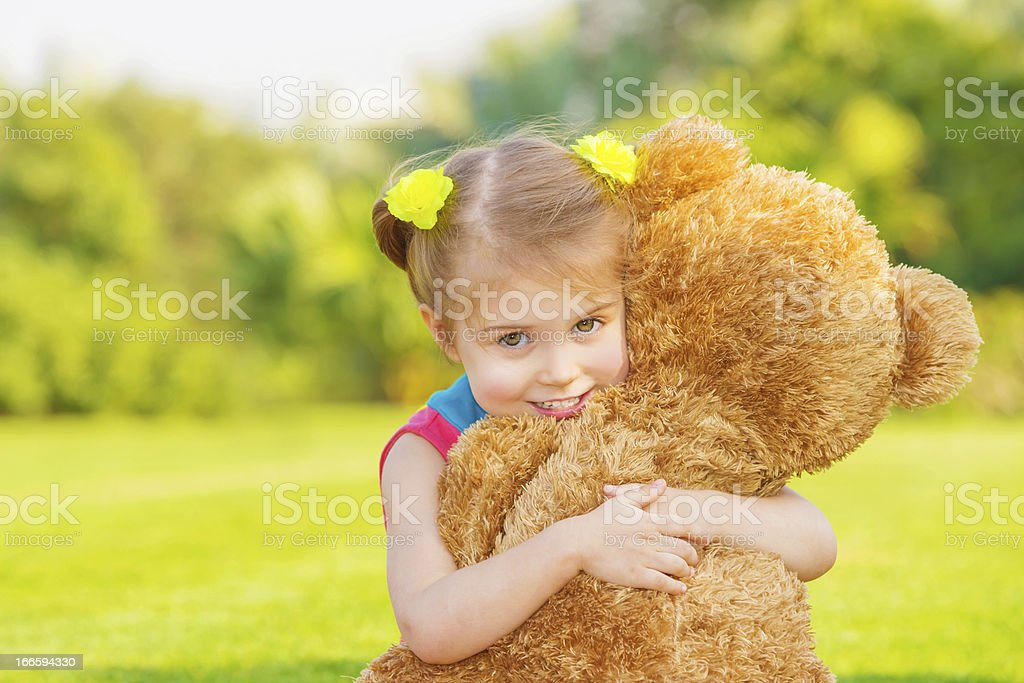 Young girl happily hugging a huge teddy bear royalty-free stock photo