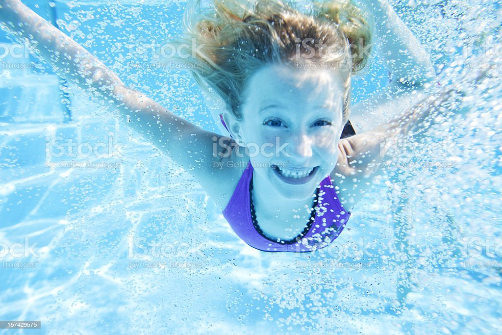 A young girl happily swimming in a pool royalty-free stock photo