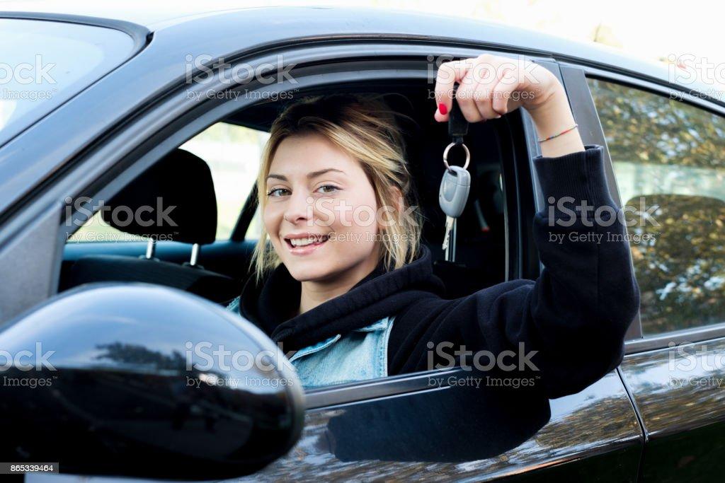 Junges Mädchen glücklich sitzt in ihrem neuen Auto Auto-Taste gedrückt halten – Foto