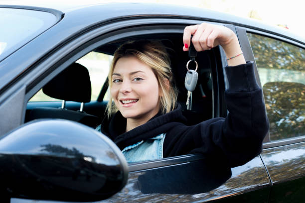 young girl happy holding car key seated in her new car - driver stock photos and pictures