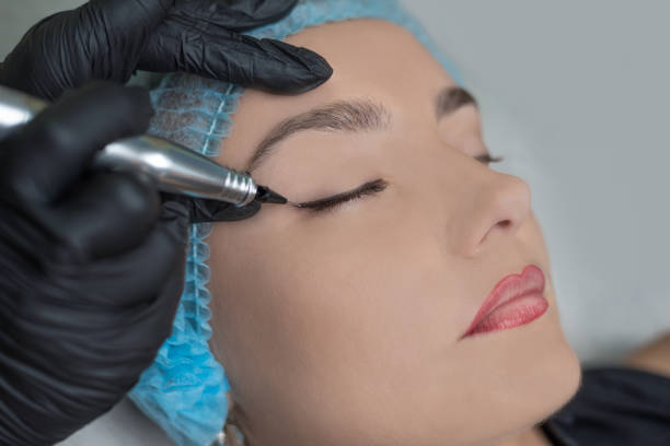 a young girl having eyeliner and eyebrows, permanent makeup, micropigmentation. - permanente foto e immagini stock