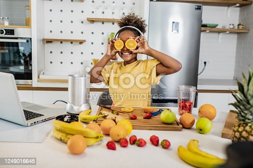 Young African American girl is in the kitchen making a healthy drink and having fun