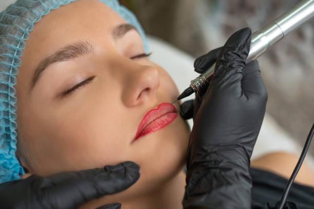 a young girl having lips permanent makeup, micropigmentation. - durabilidade imagens e fotografias de stock