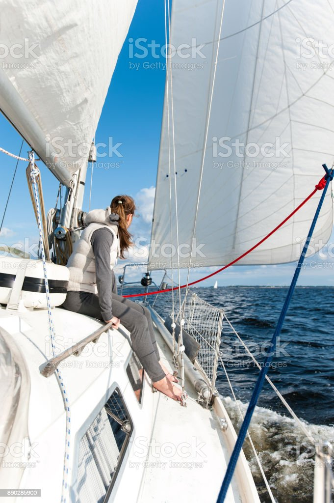 Young girl having trip on sailing yacht in windy sea stock photo