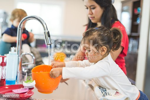 Ethnic mom helps her young daughter clean mixing bowls after baking while little brother looks on from his high chair.
