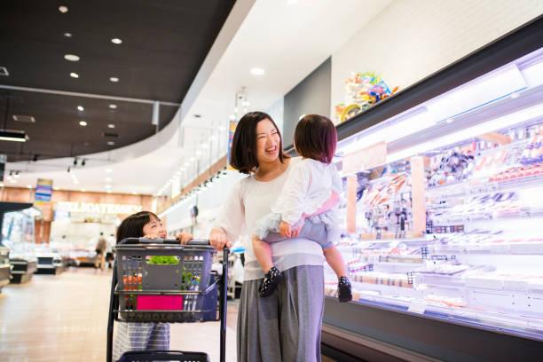 若い女の子がショッピングカートを押して彼女の母を助ける - スーパーマーケット 日本 ストックフォトと画像