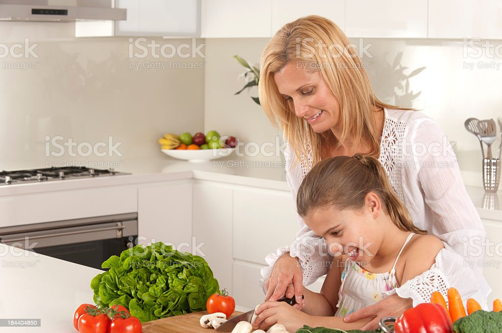 Young girl helping her mother prepare food royalty-free stock photo