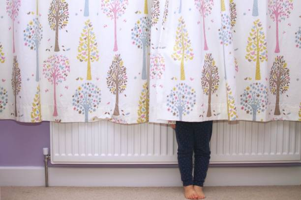 Young girl hiding behind a curtain A young girl hiding behind a curtain with only her legs showing hide and seek stock pictures, royalty-free photos & images
