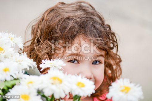A young girl hiding behind daisies
