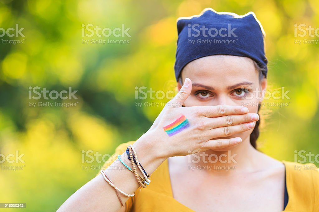 Young girl hiding her mouth stock photo
