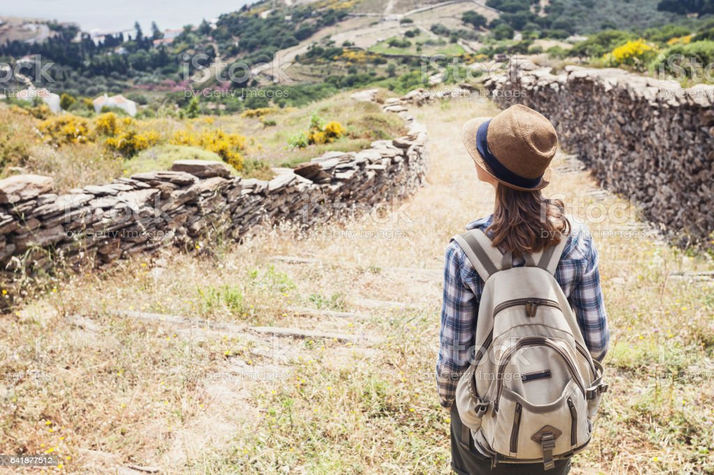 Young girl hiker on mountain trail footpath stock photo