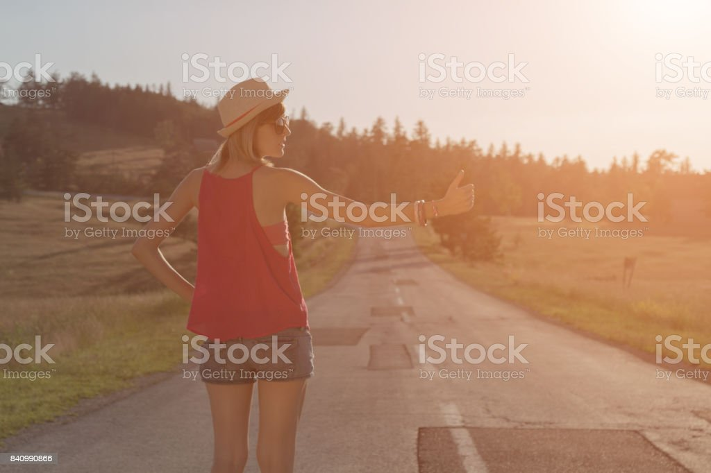 Young girl hitchhiking on the countryside road. stock photo