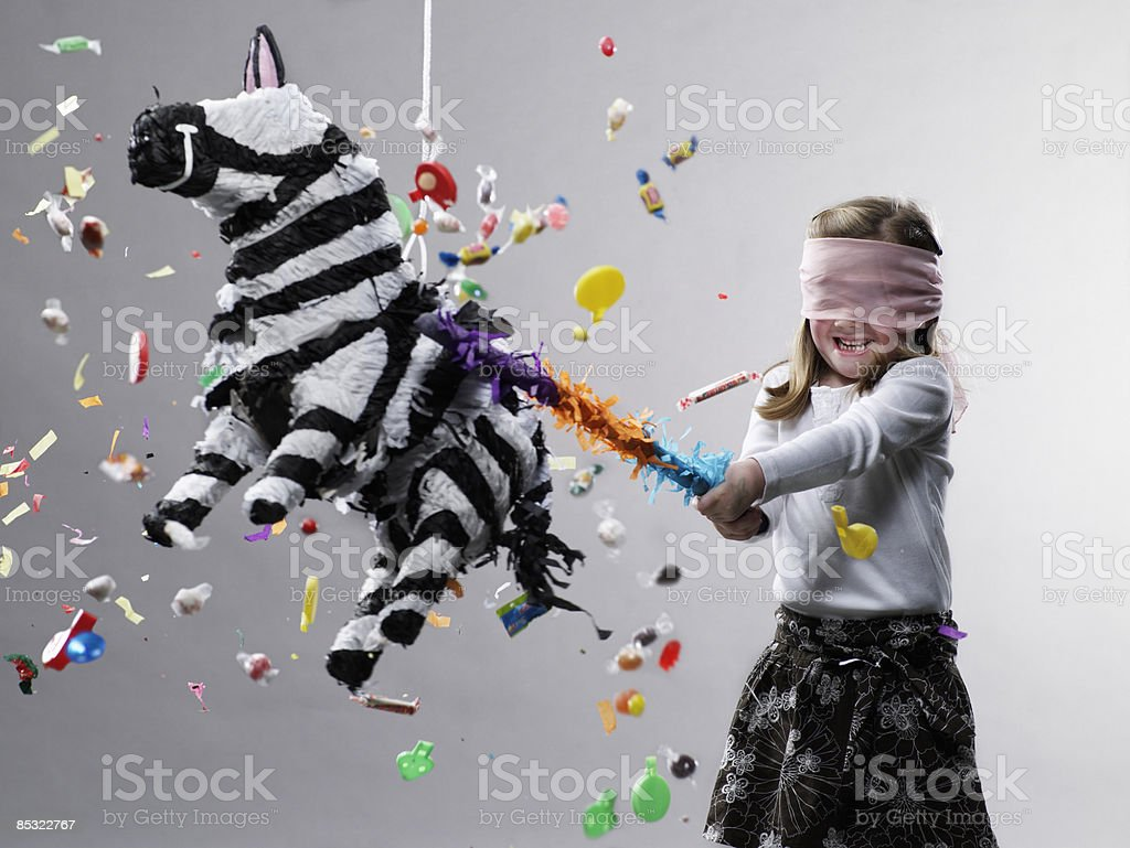 Young girl hitting pinata, candy flying 免版稅 stock photo