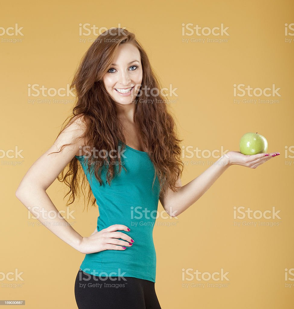 young girl holding a green apple smiling royalty-free stock photo