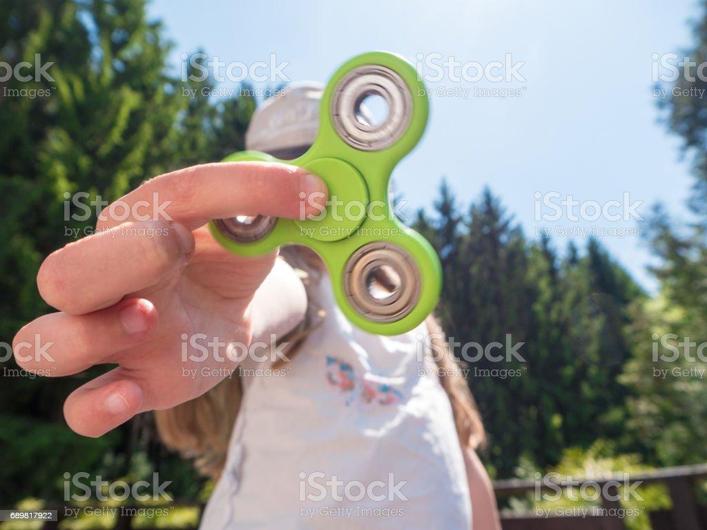 Junges Mädchen hält einen grünes Fidget Spinner im freien – Foto