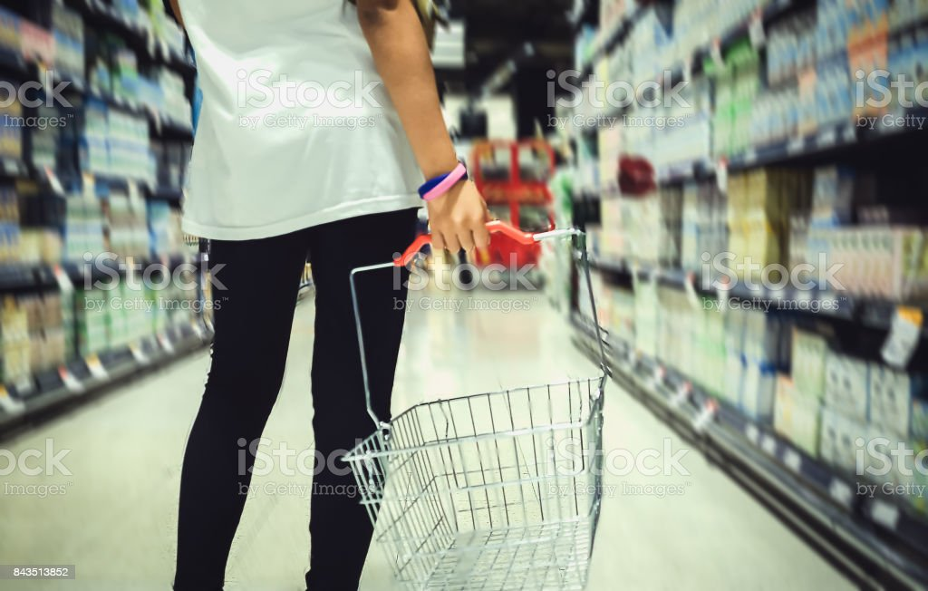 A young girl holding a shopping basket A blurred background