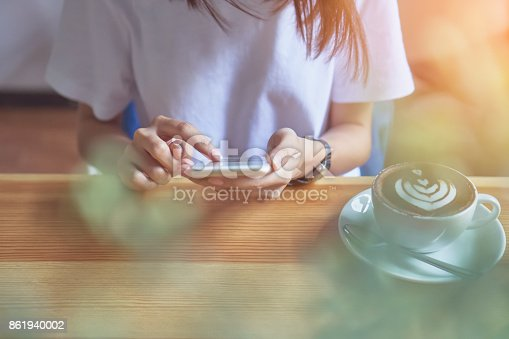 istock Young girl holding a white phone has a blank screen in cafe, And coffee on the table to make life more relaxing. The use of technology for a happy life. 861940002
