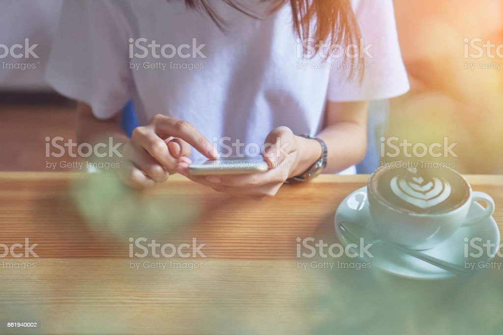 Young girl holding a white phone has a blank screen in cafe, And coffee on the table to make life more relaxing. The use of technology for a happy life. stock photo