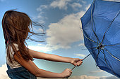 Young woman holding broken blue umbrella on a windy rainy day.