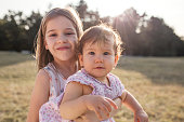 Young beautiful girl holding her baby sister in park on summer day